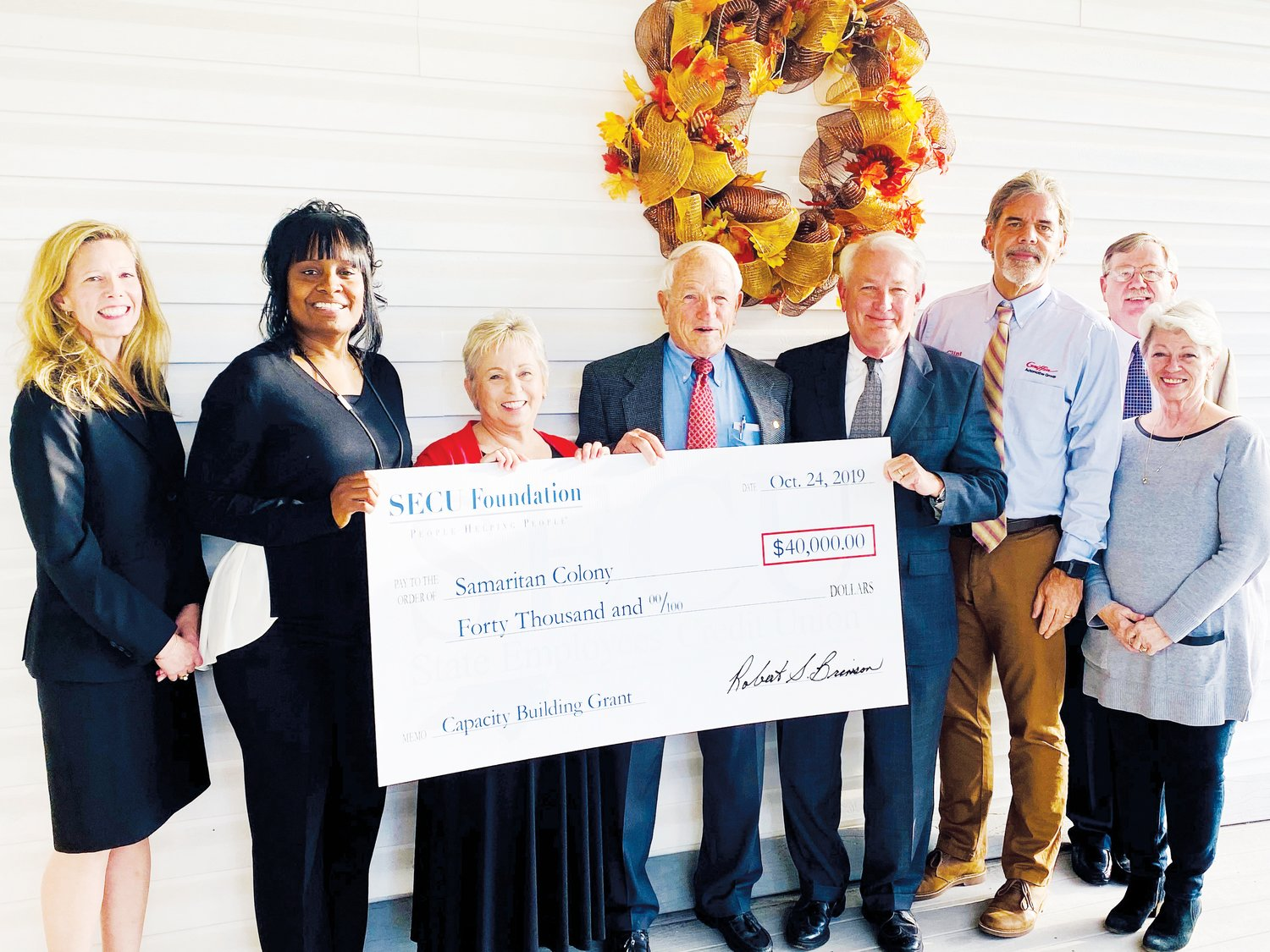 SECU Foundation representatives, including SECU Foundation Board Chair Bob Brinson (pictured fourth from the right), present a ceremonial capacity building grant check to Samaritan Colony officials.