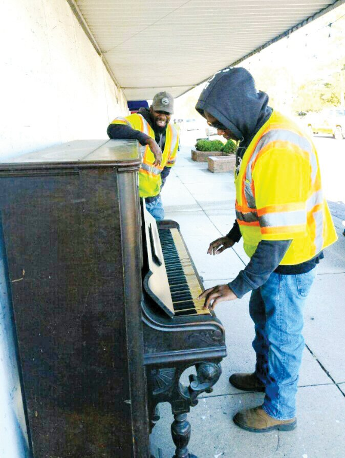 Mount Olive Public Works employees Anthony Simmons tickles the ivories as Sarome Applins look on. The two set up the piano in front of the Mount Olive Area Chamber of Commerce office on Center Street. The piano was donated to the town free for anyone to play.
