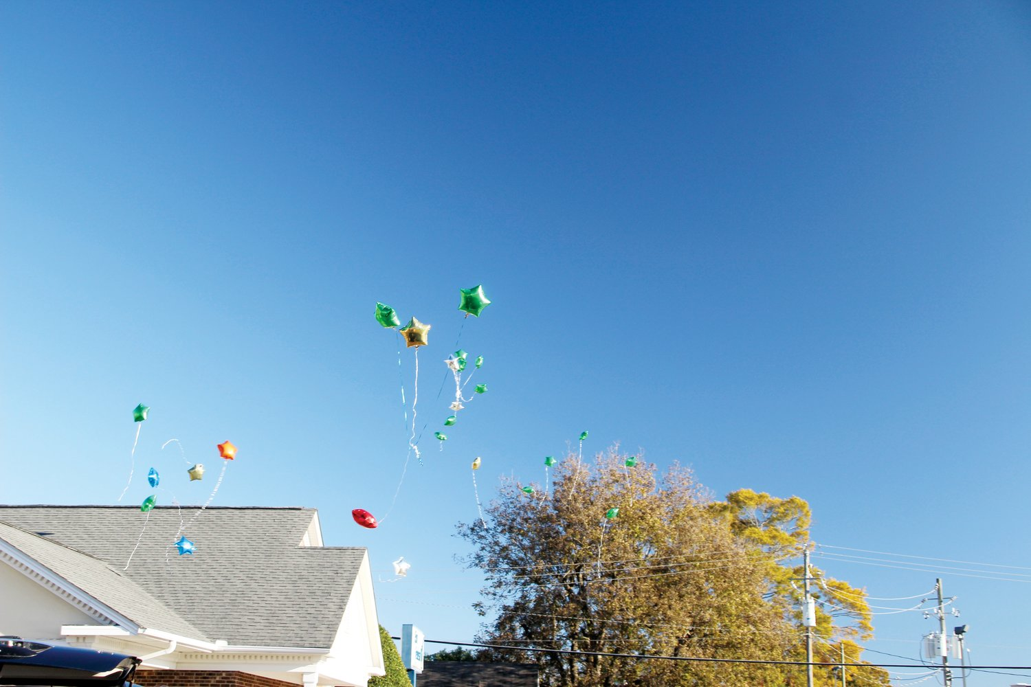 Balloons soar to a cloudless sky at a Cole Thomas memorial service Sunday.