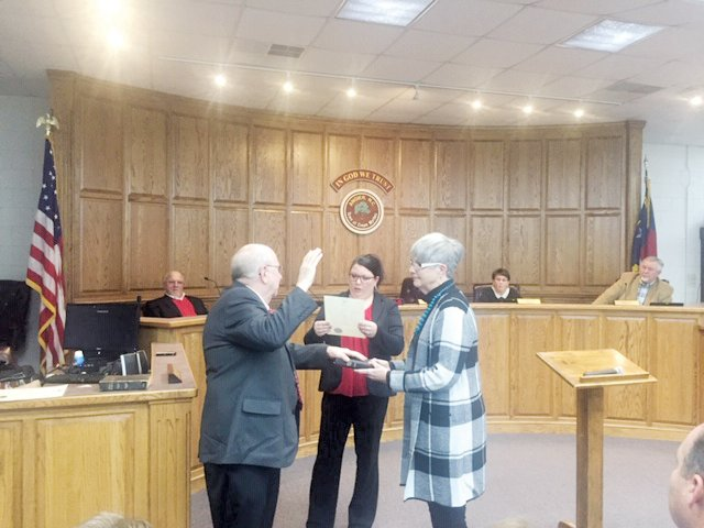 New Angier officials sworn-in...Angier town board member Bob Smith takes the oath of office during a ceremony before the start of the town board of commissioners meeting Tuesday night. Town Clerk Veronica Hardaway administers the oath as Smith's wife, Bobbi, holds the Bible.