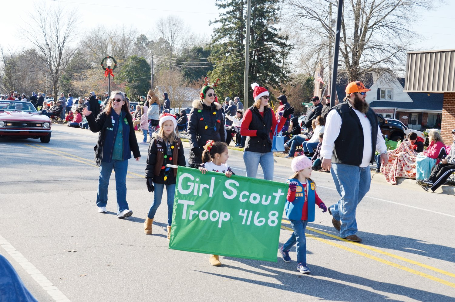 Girl Scout Troop 4168 members make their way up Broad Street during the annual Angier Christmas Parade that was held Saturday morning.