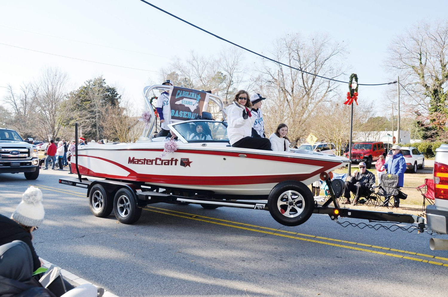 World renowned professional water skier April Coble, who grew up in the Angier area, waves from the float of her family's Lillington ski school during Angier's parade Saturday morning.