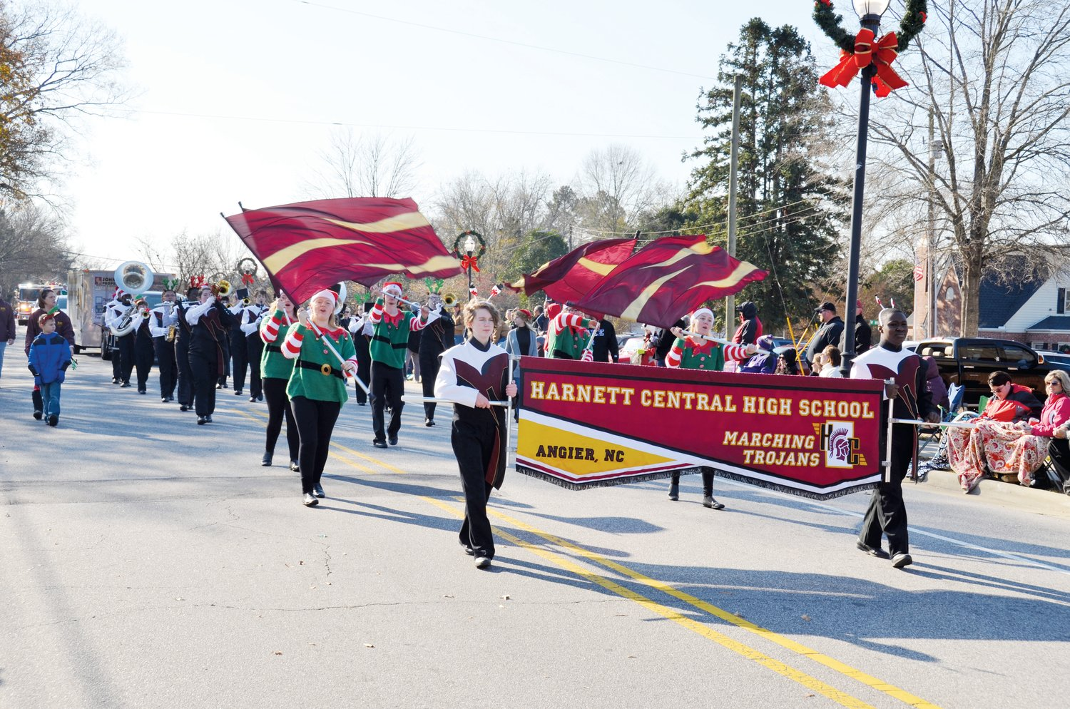 The Harnett Central Marching Trojans make their way down Broad Street in the Angier Christmas Parade Saturday. One of the largest crowds in recent memory came out for the event.