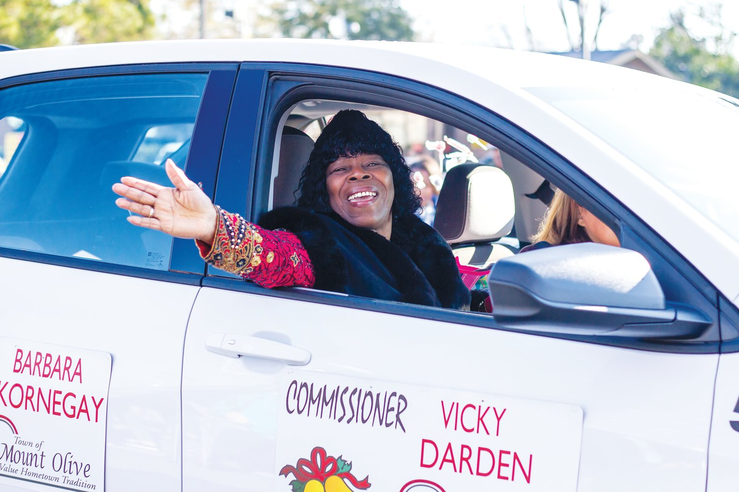 Commissioner Vicky Darden waves to bystanders and wishes them Merry Christmas as she drives by in the Mount Olive Christmas Parade.