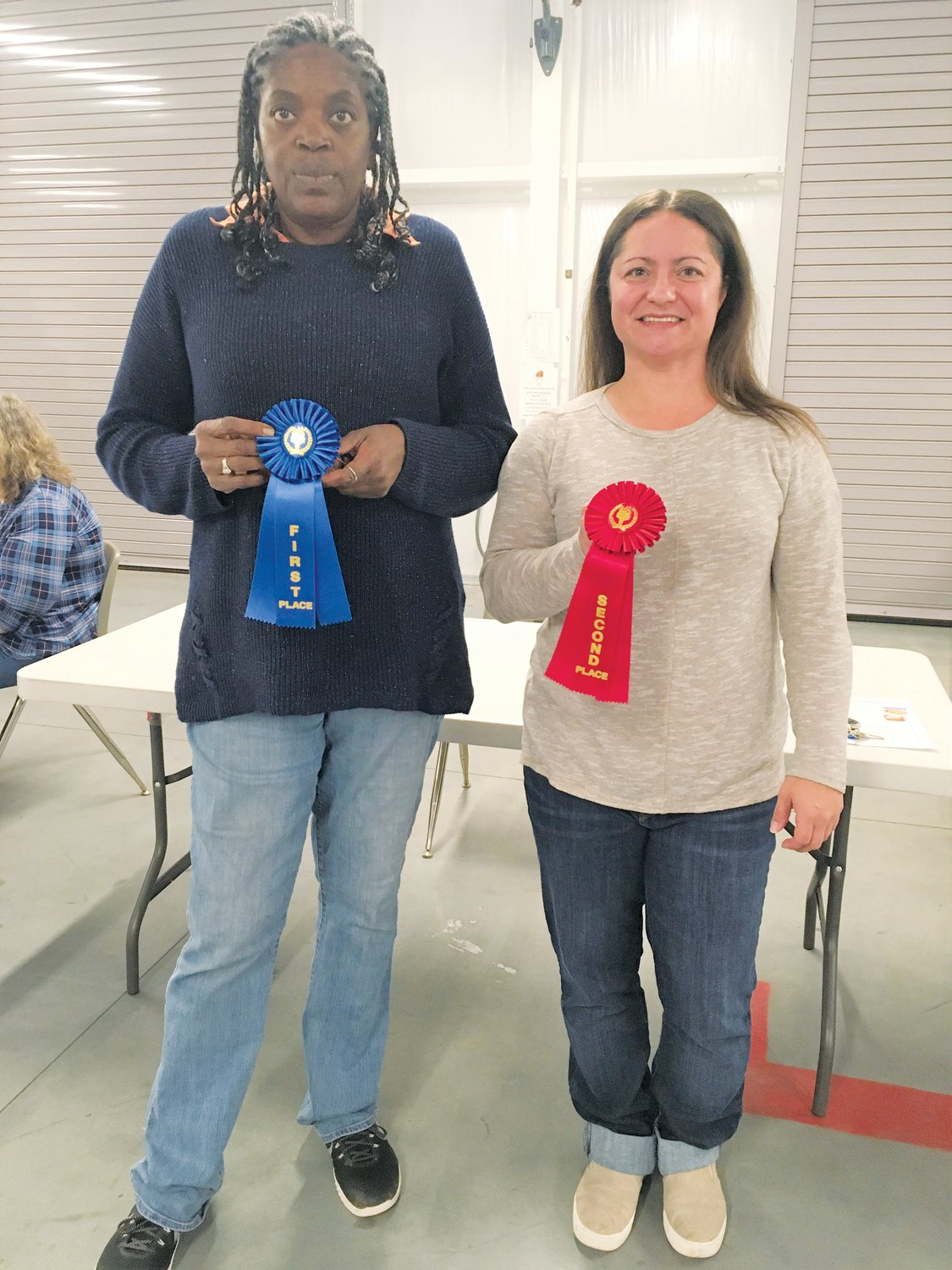 From left, Joyce Bowden of Grantham shows off her first place ribbon and Amanda Birmingham of Pikeville holds her second place ribbon for having the best dishes in the collard recipe contest at the Farm Credit Farmers Market.