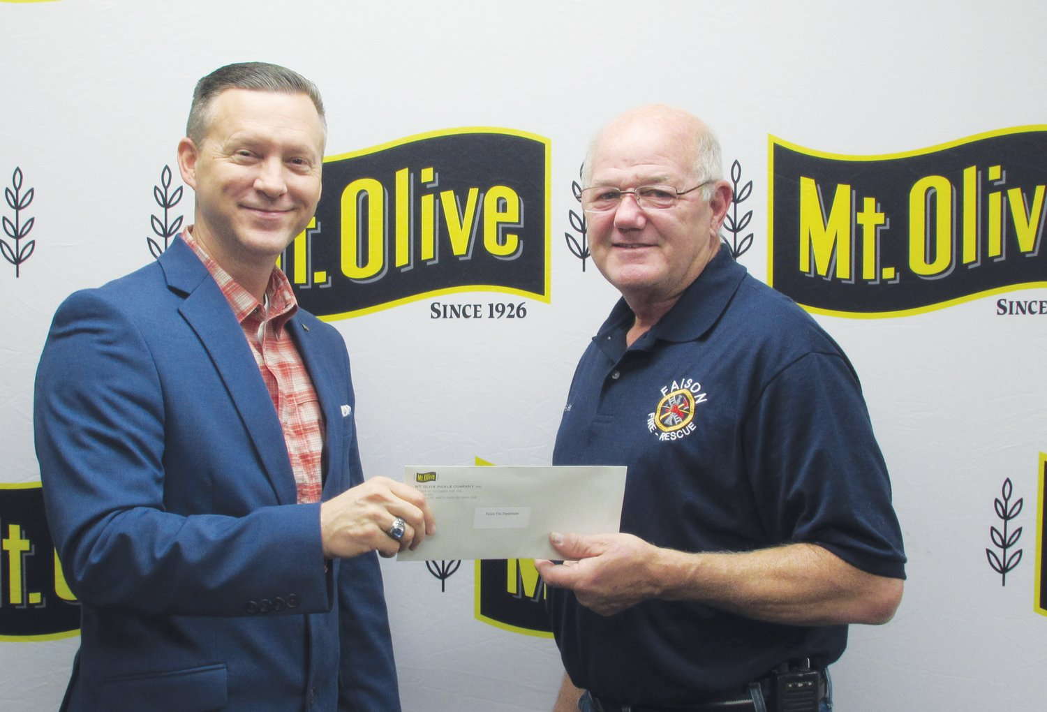 Mt. Olive Pickle Company's Employees Community Fund Chairman Patrick Muston, left, presents a check for $1,775 to Robert Kennedy, Assistant Chief of Faison Fire and Rescue.