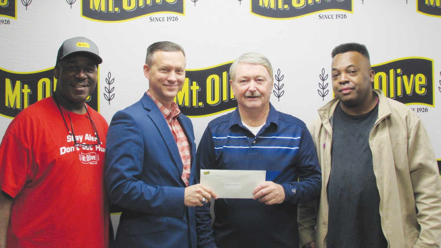Mt. Olive Pickle Company's Employees Community Fund Chairman Patrick Muston, second from left, presents a check for $1,775 to Waylon Southerland, treasurer at Pleasant Grove Volunteer Fire and EMS. Also pictured is Mt. Olive Pickle Employees Community Fund members Ronnie Core and Anthony Warren.