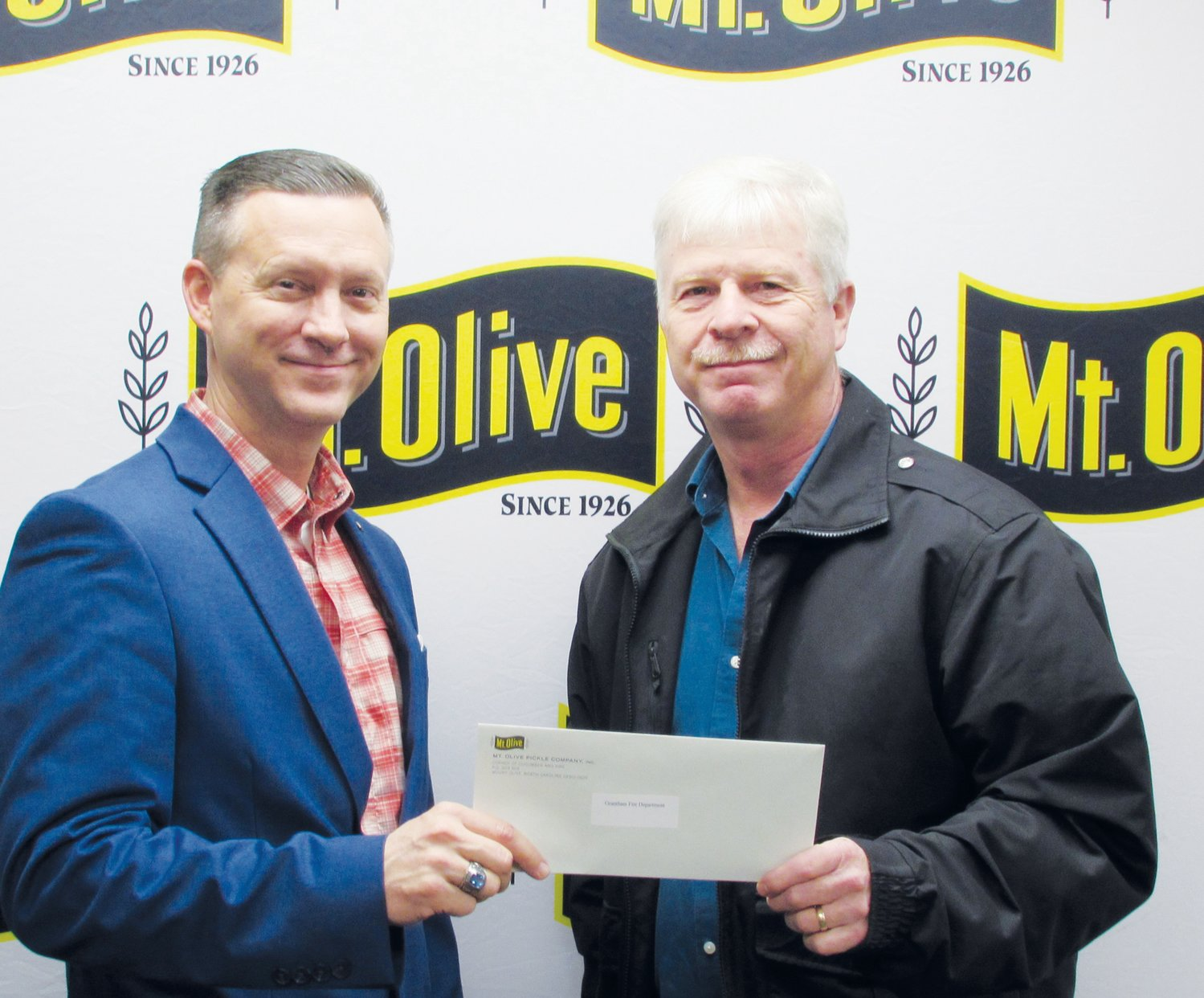 Mt. Olive Pickle Company's Employees Community Fund Chairman Patrick Muston, left, presents a check for $1,775 to Richard Proctor, Chief of Grantham Volunteer Fire Department.