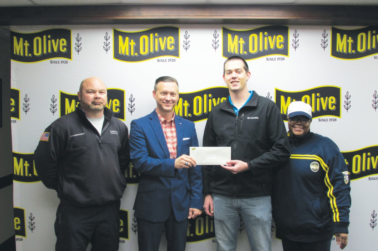 Mt. Olive Pickle Company's Employees Community Fund Chairman Patrick Muston, second from left, presents a check for $1,775 to Freddy Southerland and Brandon Lee, captains of Dudley Volunteer Fire Department. Also pictured is Mt. Olive Pickle Employees Community Fund member Michele Dortch.