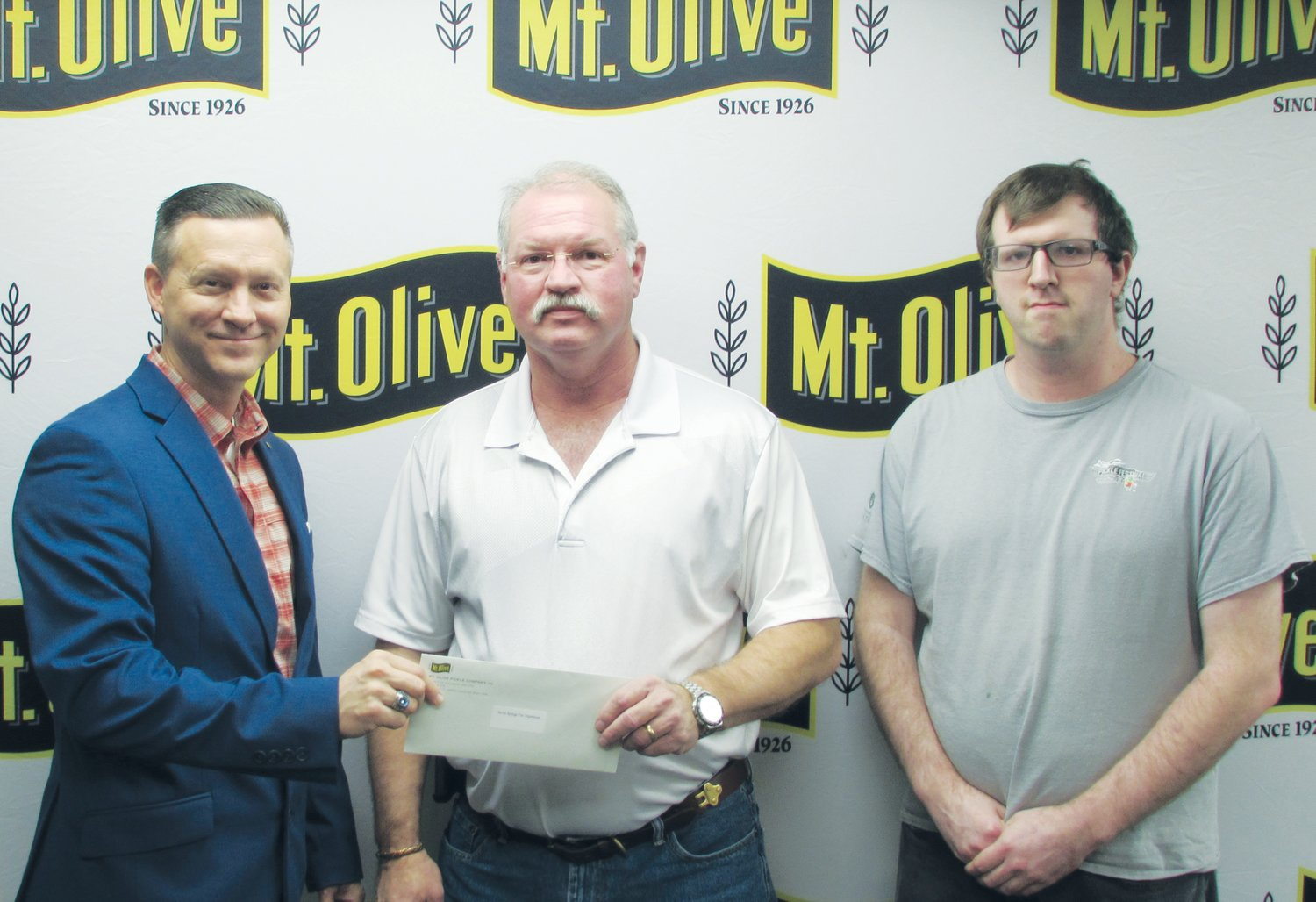 Mt. Olive Pickle Company's Employees Community Fund Chairman Patrick Muston, left, presents a check for $1,775 to Royce Shivar, a board of directors member of Seven Springs Volunteer Fire Department. Also pictured is Mt. Olive Pickle Employees Community Fund member Matthew Evrard. The Employees Community Fund contributed a total of $149,263 to 52 organizations in 2019.