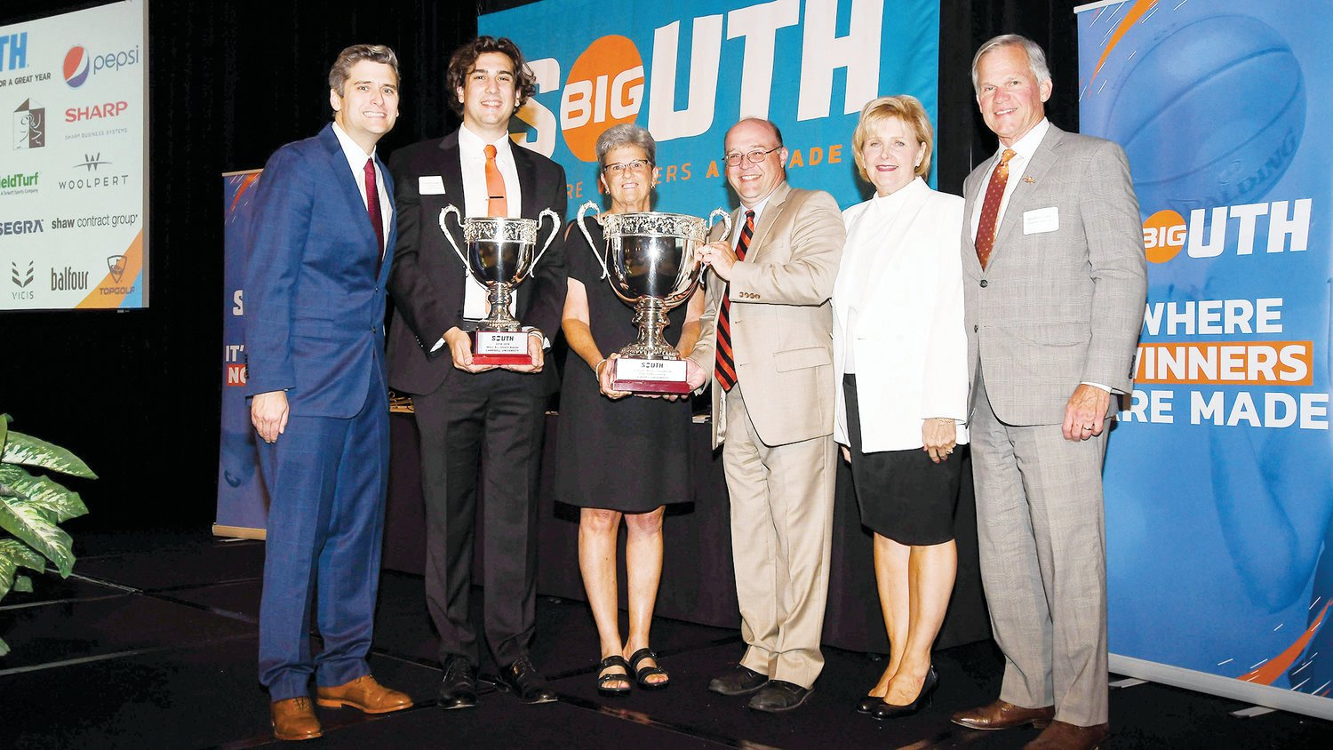 Campbell Director of Broadcasting Chris Hemeyer, Student-Athlete Advisory Committee President Cameron Kelshaw, Interim Athletic Director Wanda Watkins, Faculty Athletics Representative Dr. Sal Mercogliano, Kathy Creed, amd University President Dr. Brad Creed all stand together after Campbell was awarded the Big South Conference Sasser Cup.