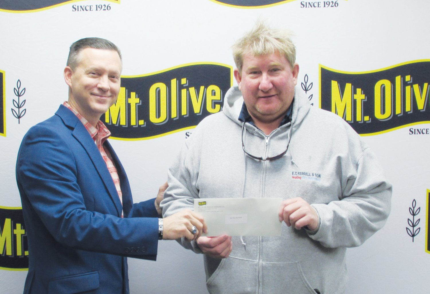 Mt. Olive Pickle Company's Employees Community Fund Chairman Patrick Muston, left, presents a check for $945 to Alex Ferrell, president and head coach of the Mount Olive Hurricanes Youth Football.