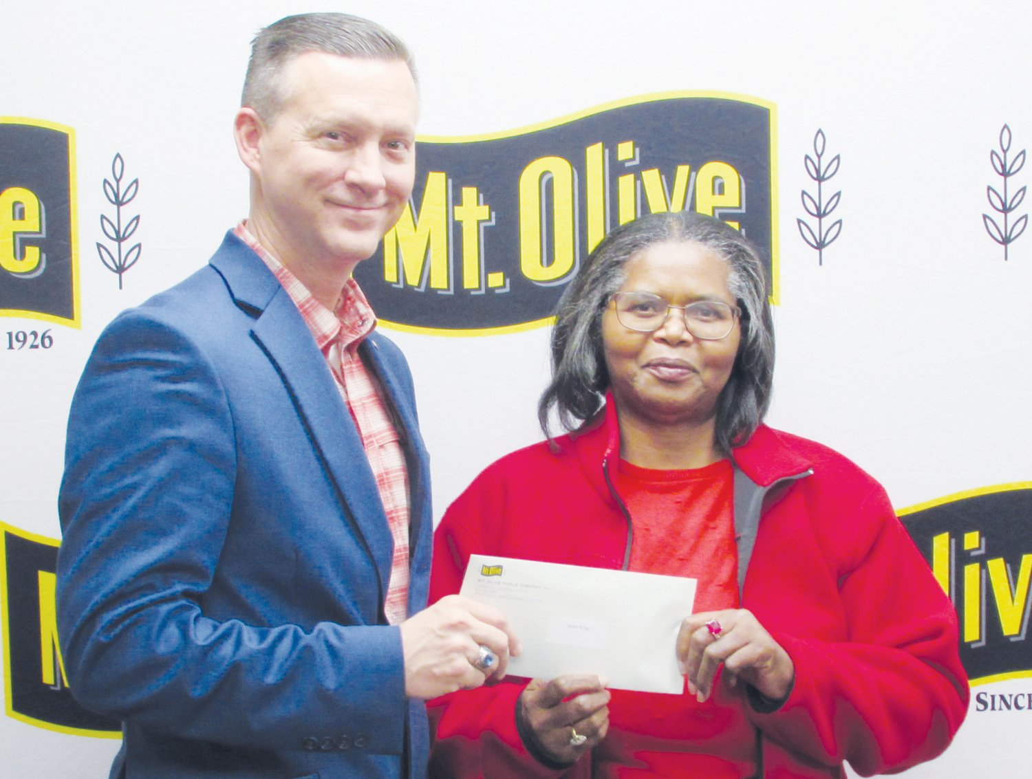 Mt. Olive Pickle Company's Employees Community Fund Chairman Patrick Muston, left, presents a check for $1,955 to Mavis Smith, chair of Sarah's Refuge in Warsaw.