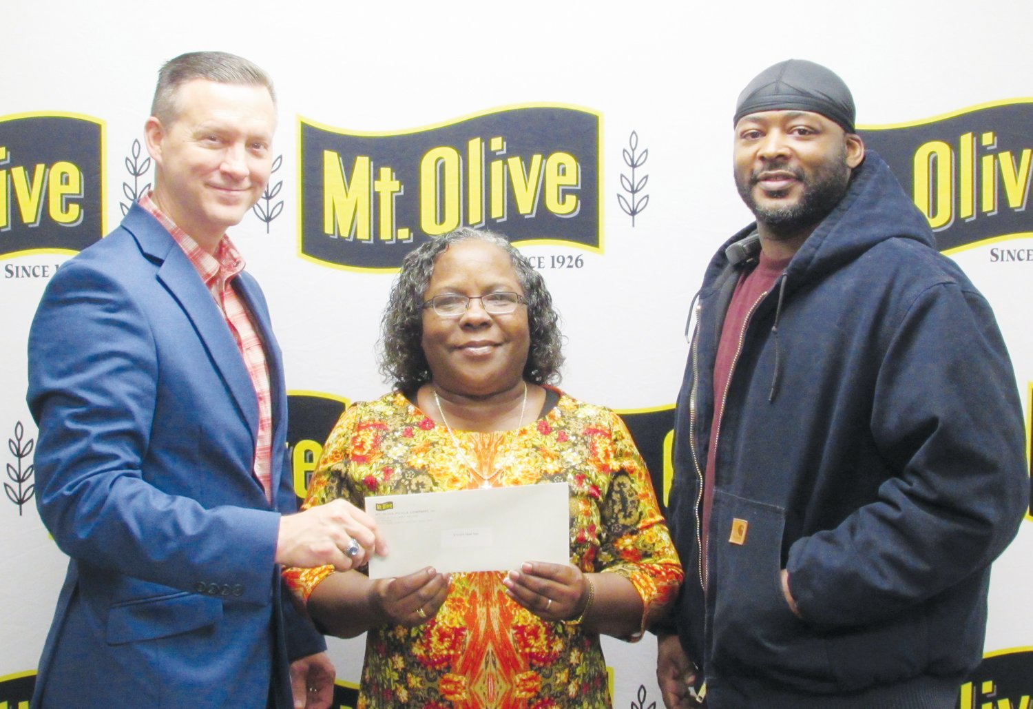 Mt. Olive Pickle Company's Employees Community Fund Chairman Patrick Muston, left, presents a check for $965 to Betty Faison, center director for WAGES Head Start. Also pictured is Mt. Olive Pickle Employees Community Fund member Tony Darden.