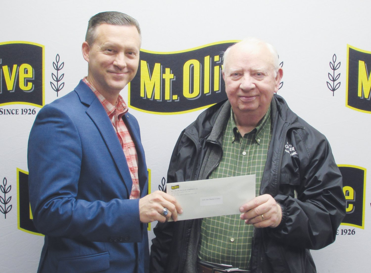 Mt. Olive Pickle Company's Employees Community Fund Chairman Patrick Muston, left, presents a check for $1,595 to Frank Harrison, president of Area Churches in Action.