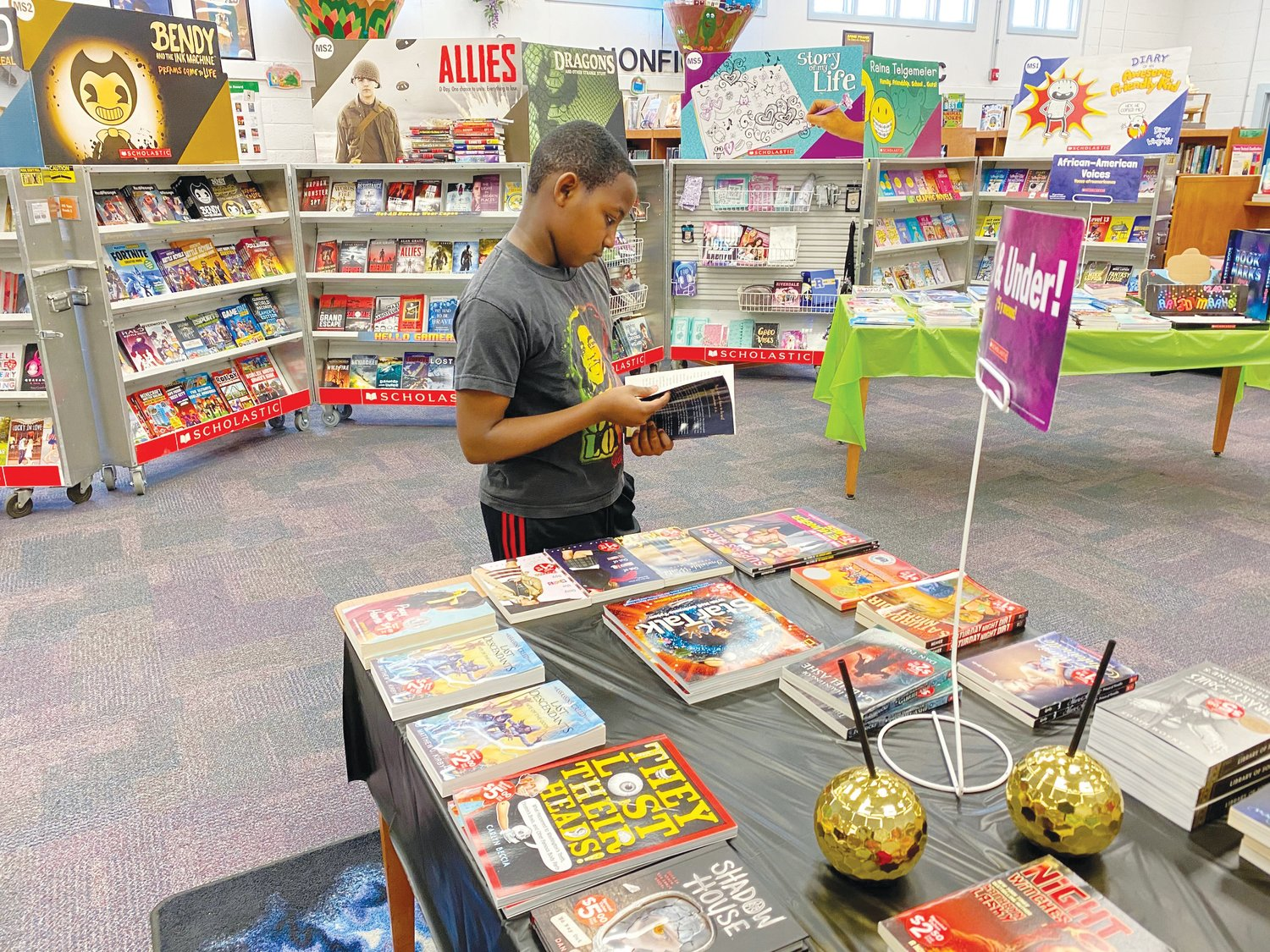 Kids make selections at local book fair.Fifth-grader Zymeer Vick thumbs through a book during last week's book fair at Mount Olive Middle School.