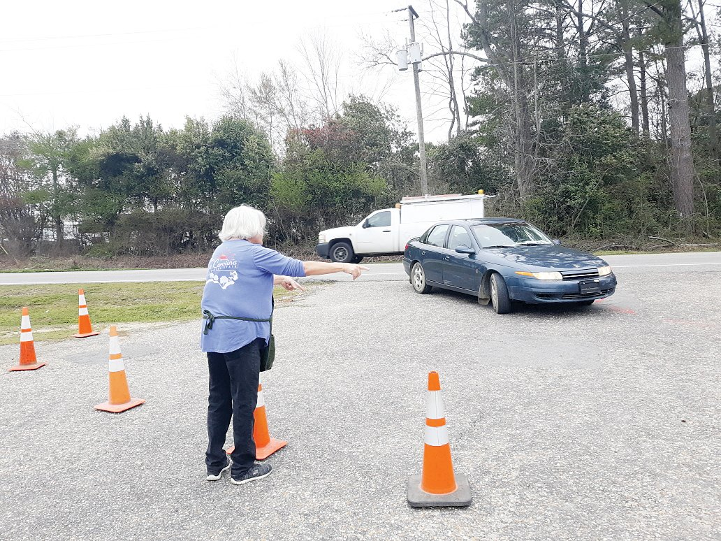 Carolyn Cox directs traffic Tuesday at the Harnett Food Pantry.