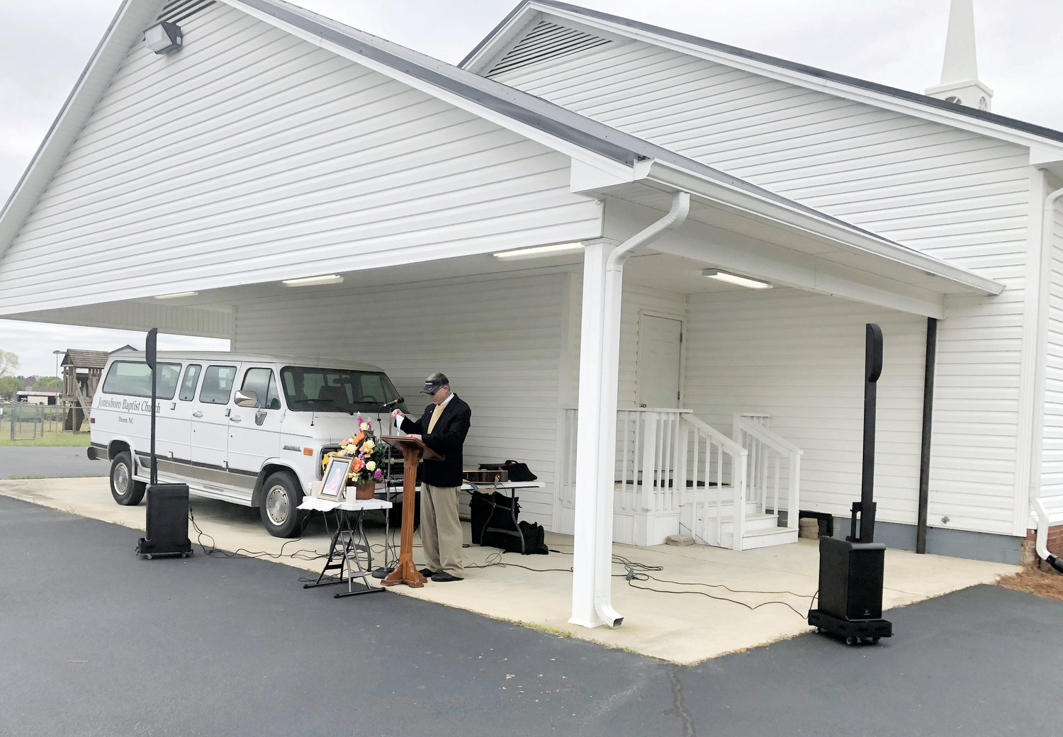 Separately worshiping together..The Rev. Charles Price leads a service before a parking lot full of cars, holding parishioners Sunday morning outside Jonesboro Baptist Church.