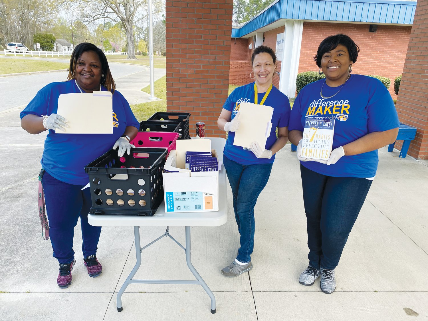 Brogden Middle School Principal Dr. Damesha Smith, left, ESL teacher Nydia Lopez, center, and Assistant Principal Kamesha Johnson pass out packets to parents during a food distribution day last Thursday.