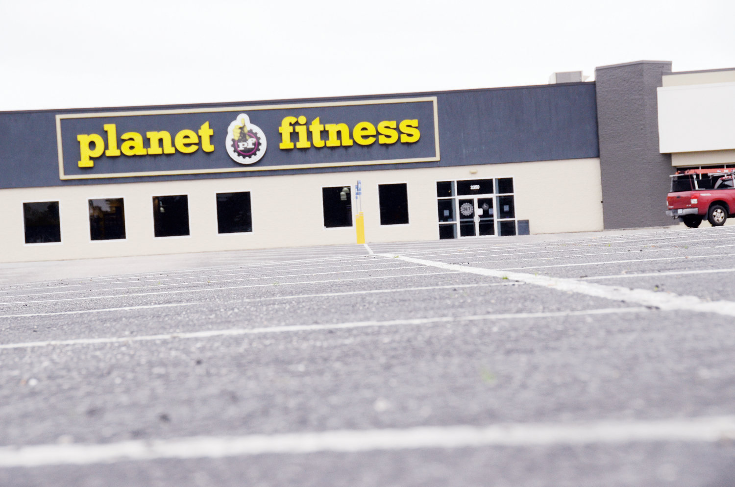Usually full of cars, the parking lot outside of Planet Fitness sits empty Tuesday after the governor ordered certain businesses like gyms and spas to shut down through May due to COVID-19.