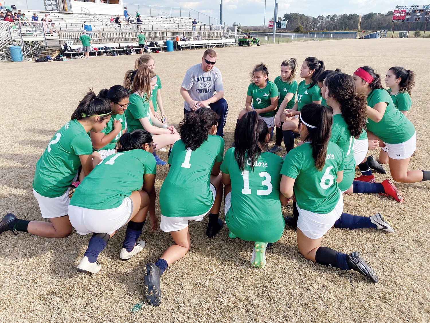Spring Creek High School girls' soccer coach Daniel Robinson, back center, speaks with his team before its final game of the season in March.