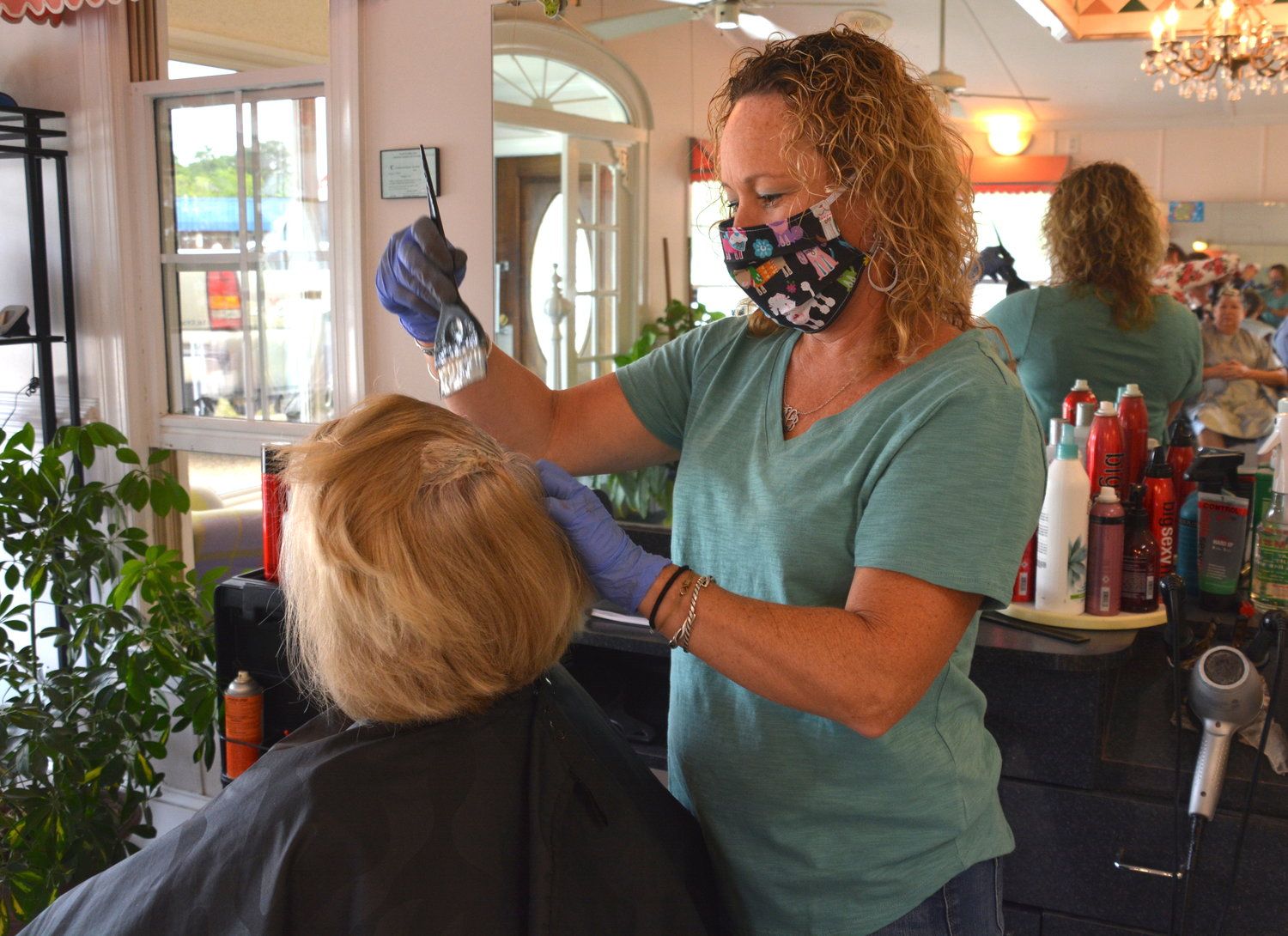 Bridget Lee works on a client's hair at Plain & Fancy Tuesday. She reopened her beauty salon this week after it was shuttered in March to prevent the spread of COVID-19.