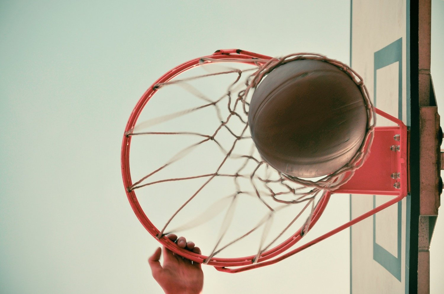 A basketball exits the net.