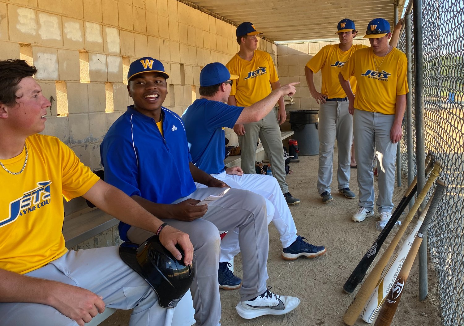 Wayne County Jets head coach Adam Pate (middle) has a teaching moment with some players in the dugout, while Tyler Daniels (second from left) and University of Mount Olive commit Blake Gipson (left) talk.