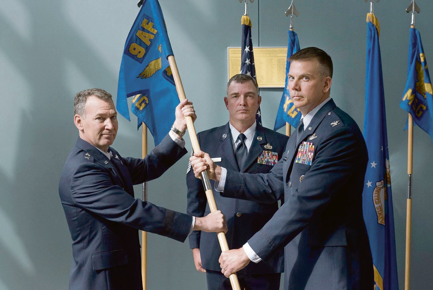 Maj. Gen. Chad P. Franks, Ninth Air Force commander (left), hands the guidon to Col. Kurt C. Helphinstine (right), incoming 4th Fighter Wing commander, during the 4 FW change of command ceremony at Seymour Johnson Air Force Base Thursday. Helphinstine was previously deputy commander for operations at the 366th Fighter Wing in Mountain Home Air Force Base, Idaho.