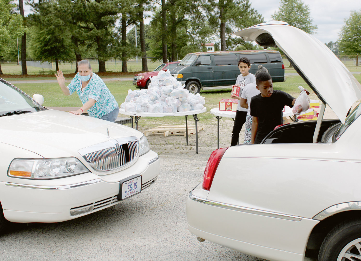 Volunteers place bags of food in the trunks of cars at the Mount Olive Food Bank, which is located at Old Carver School.
