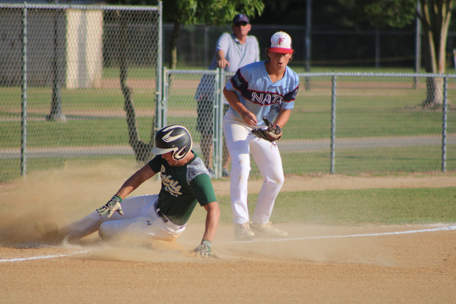 Kyle Holland, of the Mount Olive Green Machine, slides safely into third base after connecting on a bases-clearing triple during middle-inning action against the Garner Junior Nats on Thursday evening.