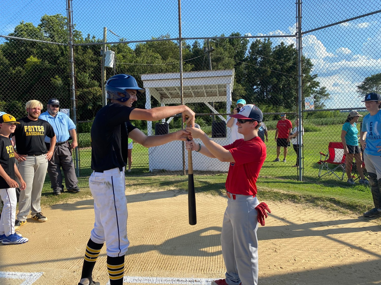 Potter's Baseball Tour player Bryan Shirkey, left, and Mount Olive Green Machine's Wyatt Womble decide which team bats first during an exhibition game at Daughtry Field on Sunday evening. PBT claimed the chance to bat first.