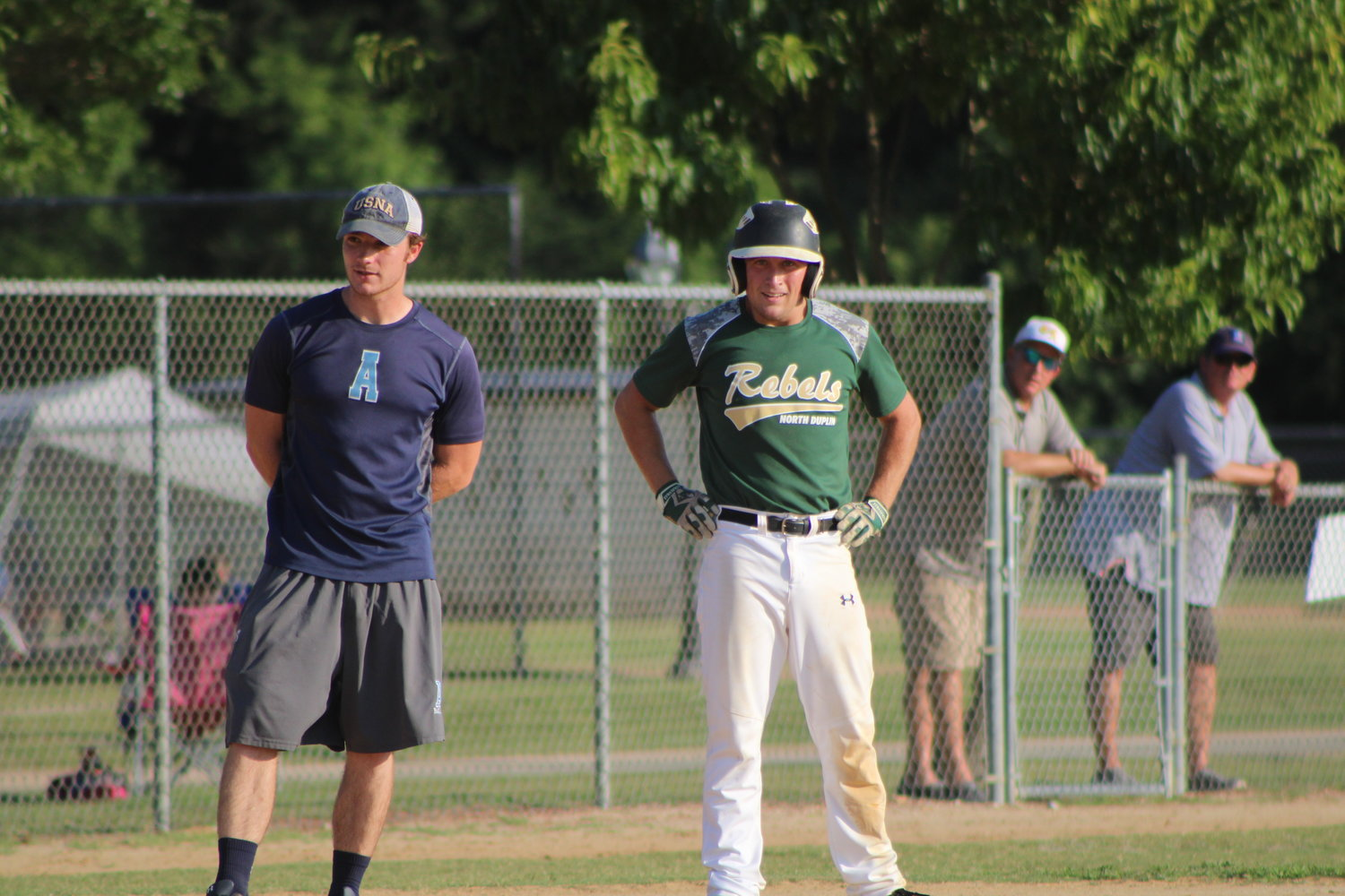 The Mount Olive Green Machine's Kyle Holland (right) stands at third base with associate head coach Braxton Leeper during a recent game. Holland, who just celebrated a birthday, delivered a key middle-inning double during the Machine's 5-3 triumph over the Garner Junior Nats on Monday.