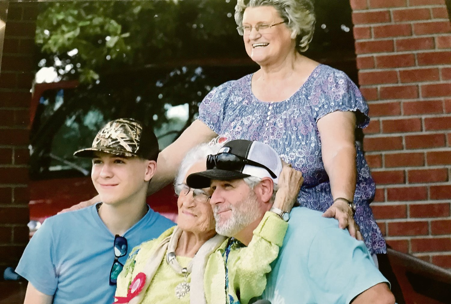 Matoaka Westbrook, center, hugs up to her family for a photo during the parade honoring her 100th birthday Aug. 15. From left, are Westbrookâ??s great grandson, Tadan Ivey; Westbrook; Westbrookâ??s grandson, Billy W. Ivey; and Westbrookâ??s daughter, Joan Ivey, standing.