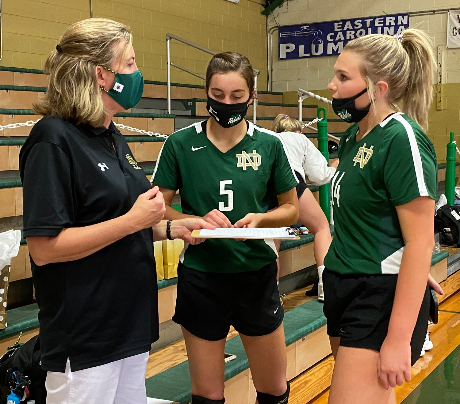North Duplin head volleyball coach Laura Thornton, left, talks with her daughter Callie (5) and Morgan McCoy (14) about the starting rotation before Tuesday's match against Hobbton.
