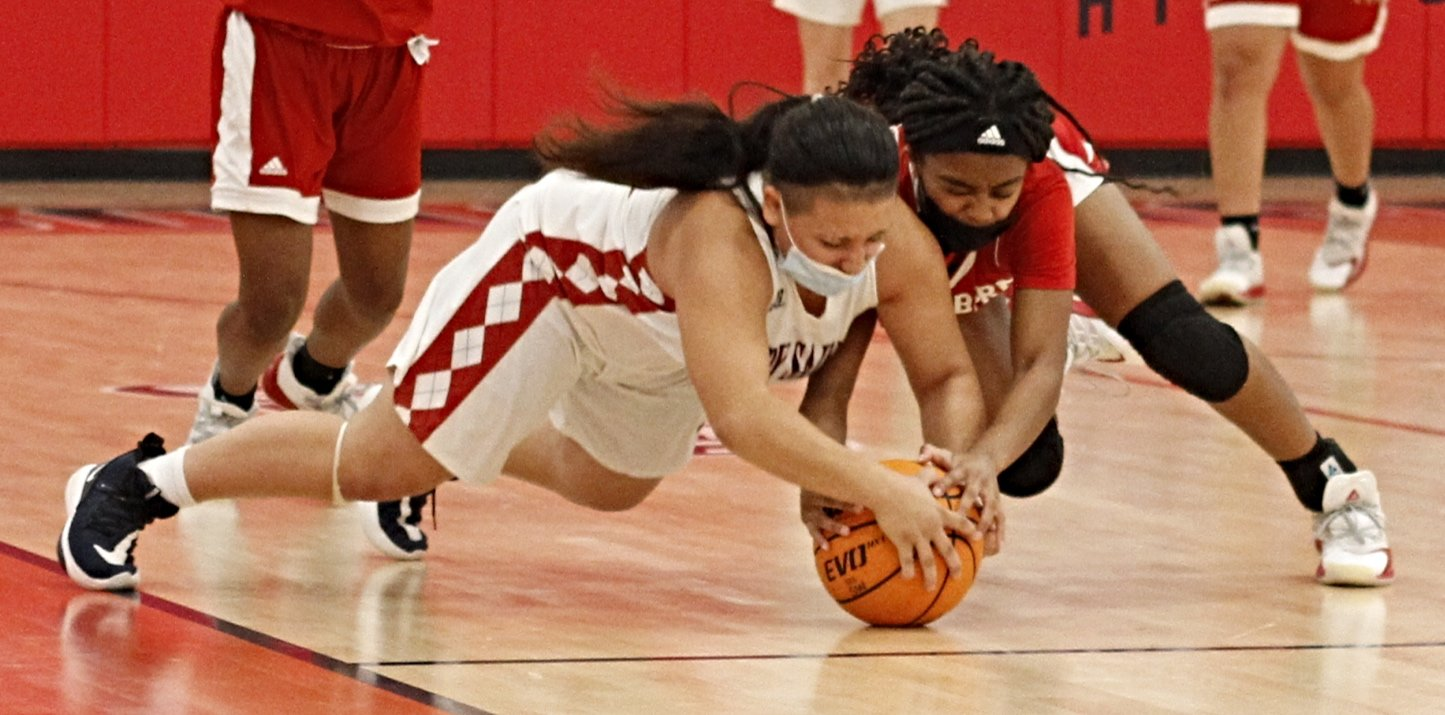 Southern Wayne's Angela Jones (left) dives to the floor for a loose ball during opening-half play against New Bern on Friday evening.