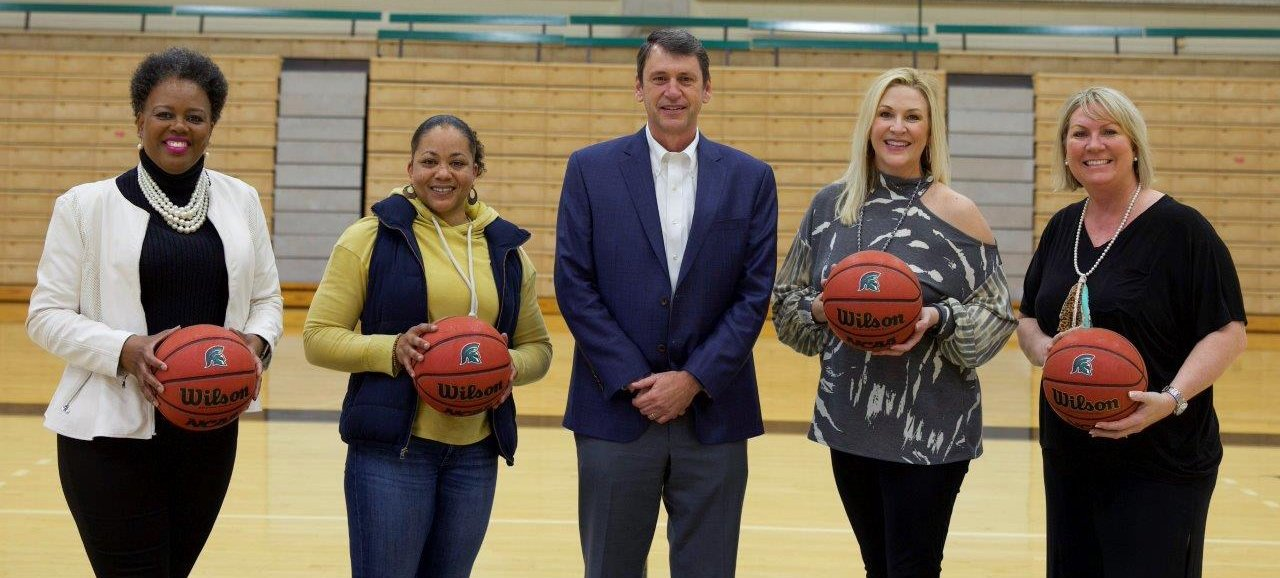 Former Mount Olive College/University of Mount Olive women's basketball players will be featured during halftime of the Church Night basketball games that will air on Jan. 30 on the university's Facebook page. Standing left to right are: Marchelle Sutton Horner (1990), Brandy Smith (2004), UMO President Dr. H. Edward Croom, Vicki Stroud Robinson (1992) and Candida Gurganus Grogg (1995).