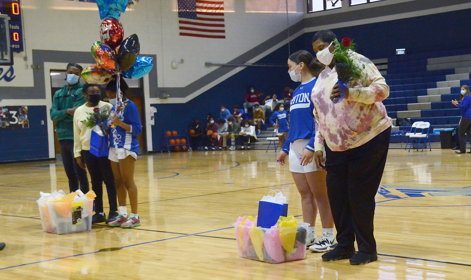 Triton girls basketball players Anastasia McDonald, left, and Kaila Cooney, right, are joined by family members during Tuesday's Senior Night ceremony. Six seniors from the boys' basketball team were also honored.