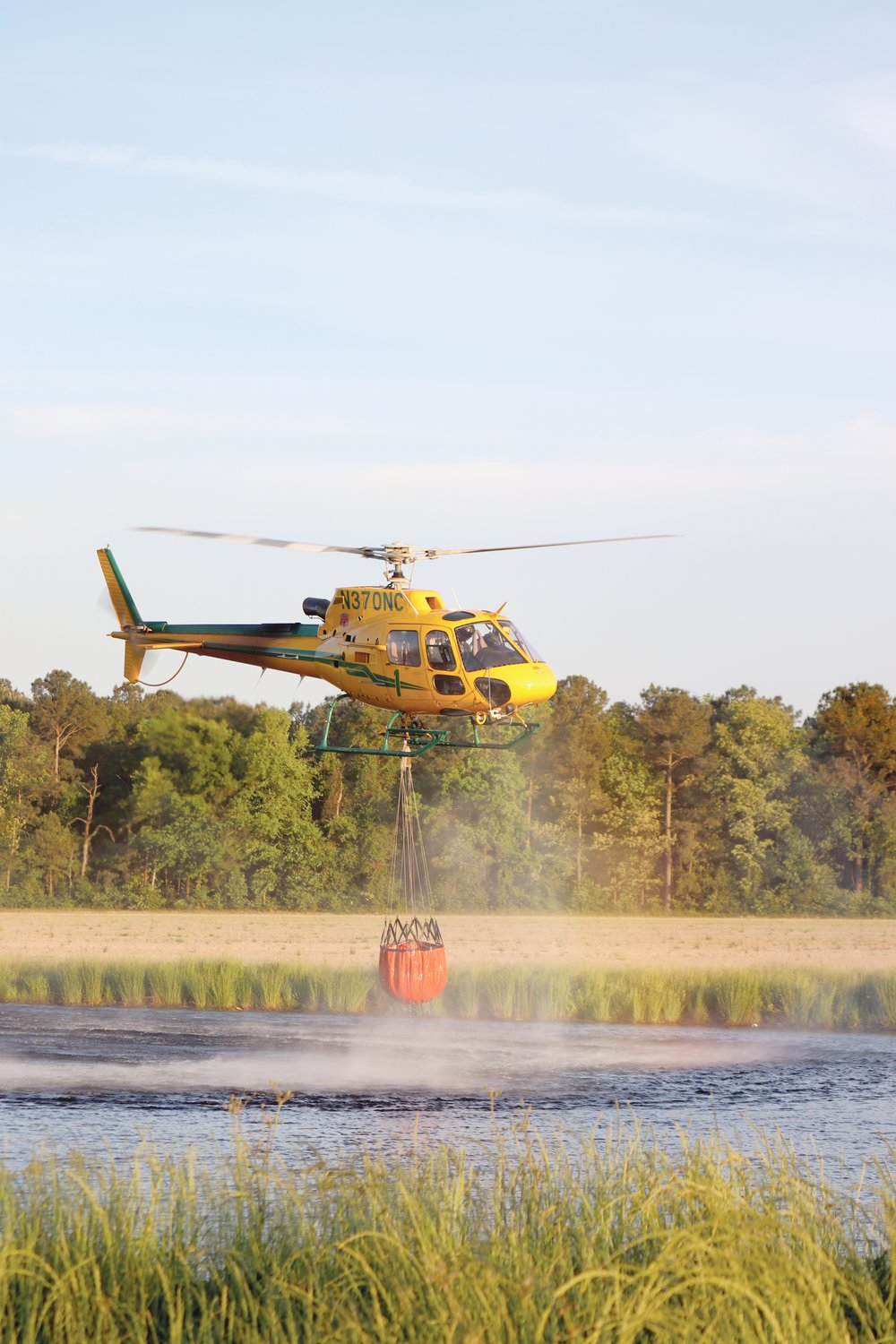 An N.C. Forestry Service helicopter picks up a load of water from a nearby retention pond to fight the blaze at the Enviva Pellet Plant Friday.