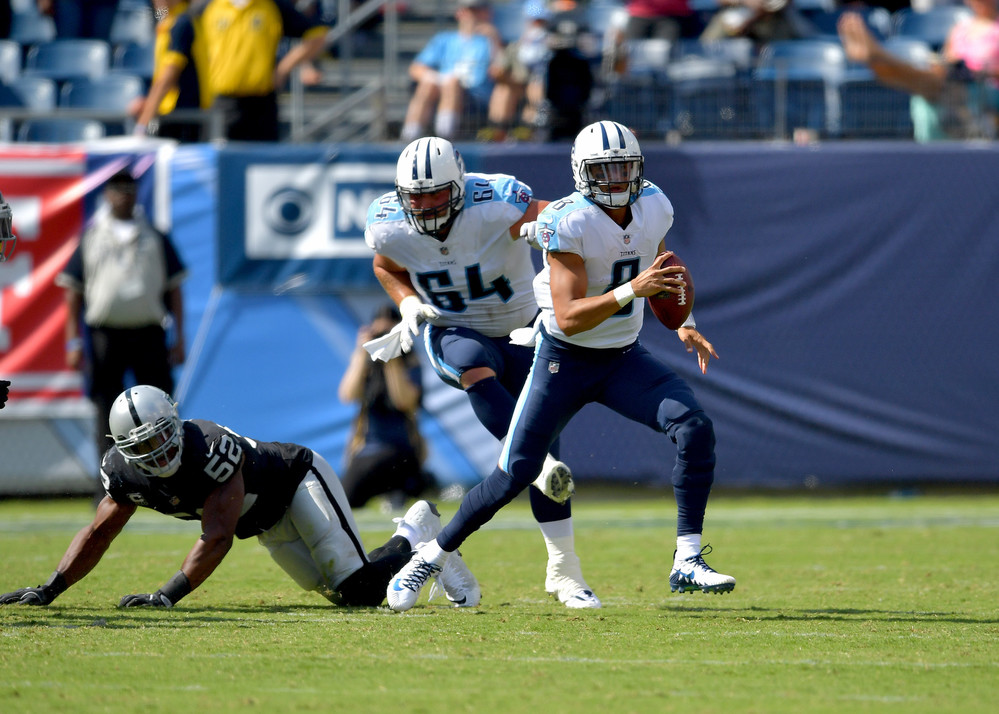 Titans quarterback Marcus Mariota (8) gets by Raiders defensive end Khalil Mack (52) and looks for a receiver in the second half of the Oakland Raiders at Tennessee Titans NFL football game on Sept. 10, 2017, at Nissan Stadium in Nashville, Tenn. Raiders won 26-16. (Photo by Lee Walls)
