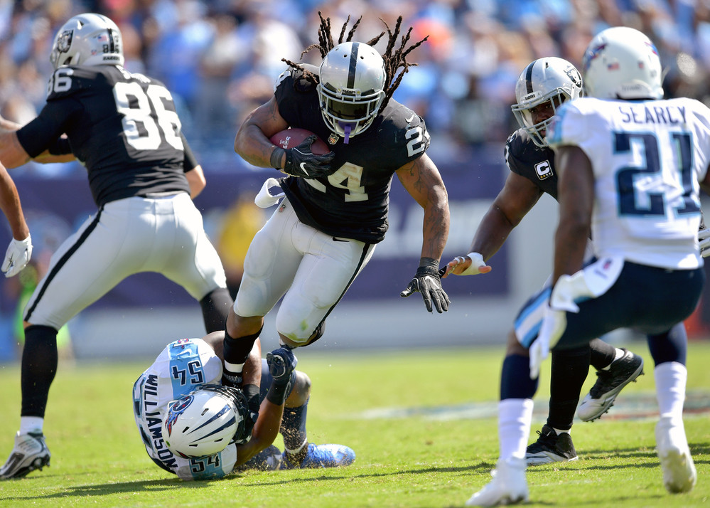 Titans inside linebacker Avery Williamson (54) tries to hold onto Raiders running back Marshawn Lynch (24) in the second half of the Oakland Raiders at Tennessee Titans NFL football game on Sept. 10, 2017, at Nissan Stadium in Nashville, Tenn. Raiders won 26-16. (Photo by Lee Walls)
