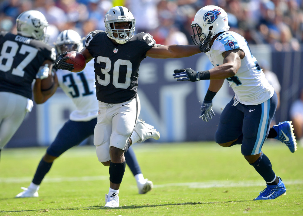 Titans inside linebacker Avery Williamson (54) gets stiff-armed by Raiders running back Jalen Richard (30) in the second half second half of the Oakland Raiders at Tennessee Titans NFL football game on Sept. 10, 2017, at Nissan Stadium in Nashville, Tenn. Raiders won 26-16. (Photo by Lee Walls)