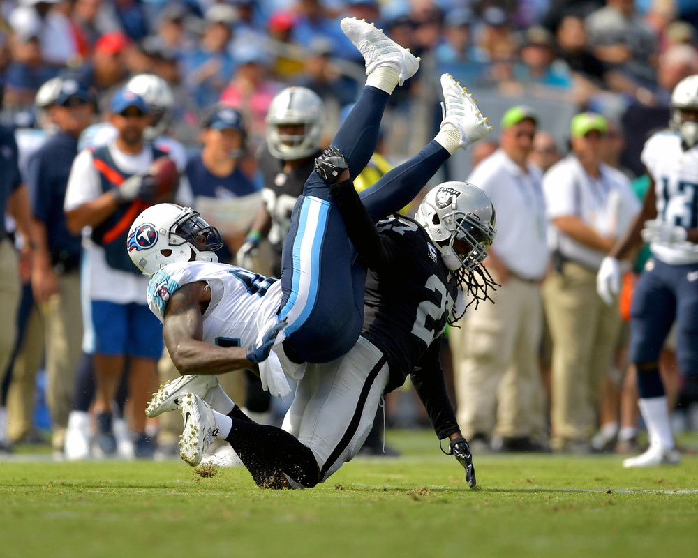 Titans tight end Delanie Walker (82) is upended by Raiders free safety Reggie Nelson (27), but hangs onto the catch during the second half of the Raiders at Titans NFL football game on Sept. 10, 2017, at Nissan Stadium in Nashville, Tenn. Raiders won 26-16. (Photo by Lee Walls)