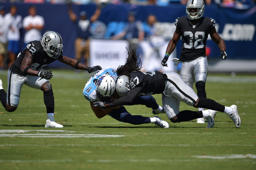 Raiders free safety Reggie Nelson (27) hits Titans quarterback Marcus Mariota (8) as Mariota drops to the ground in the first half of the Raiders at Titans NFL football game on Sept. 10, 2017, at Nissan Stadium in Nashville, Tenn.