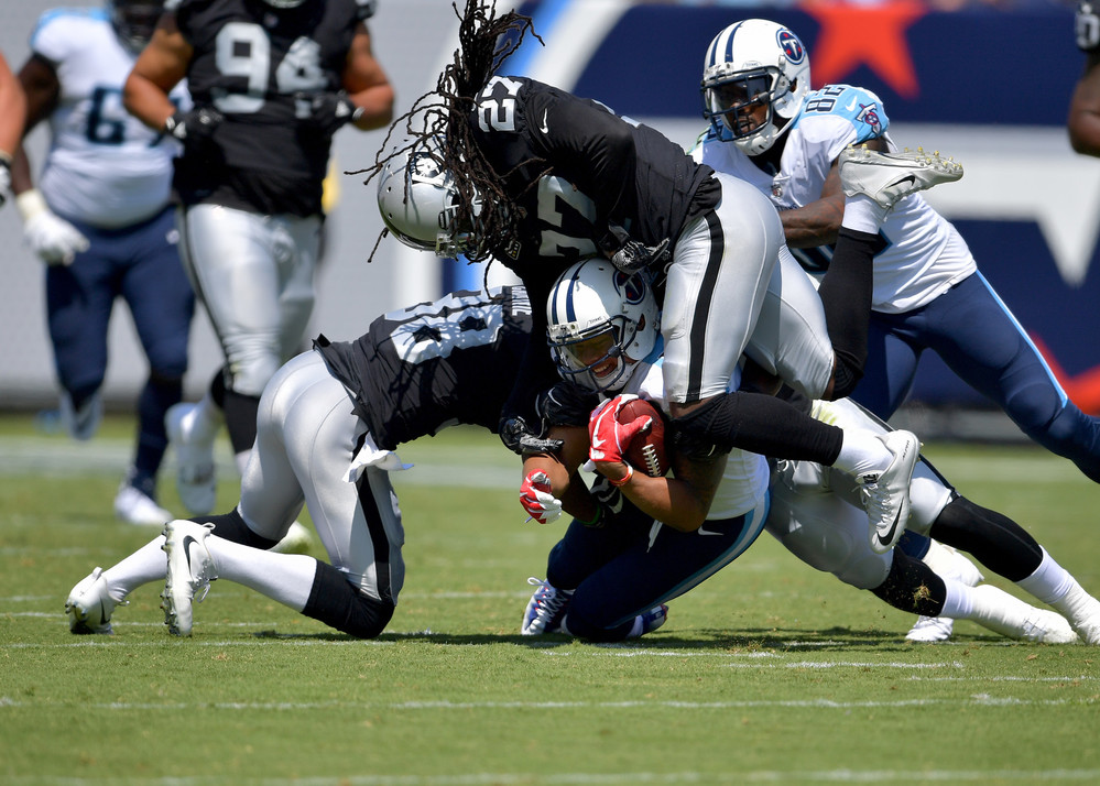 Titans wide receiver Rishard Matthews (18) holds on tight ball while being tackled in the first half of the Oakland Raiders at Tennessee Titans NFL football game on Sept. 10, 2017, at Nissan Stadium in Nashville, Tenn.