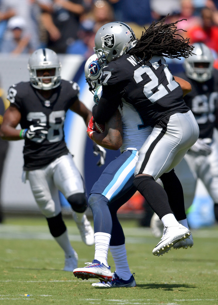 Raiders free safety Reggie Nelson (27) jumps on the back of Titans wide receiver Rishard Matthews (18) in the first half of the Oakland Raiders at Tennessee Titans NFL football game on Sept. 10, 2017, at Nissan Stadium in Nashville, Tenn.