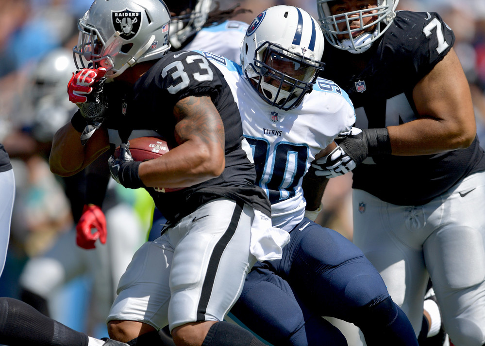 Titans defensive end DaQuan Jones (90) reaches out to stop Raiders running back DeAndre Washington (33) in the first half of the Raiders at Titans NFL football game on Sept. 10, 2017, at Nissan Stadium in Nashville, Tenn.