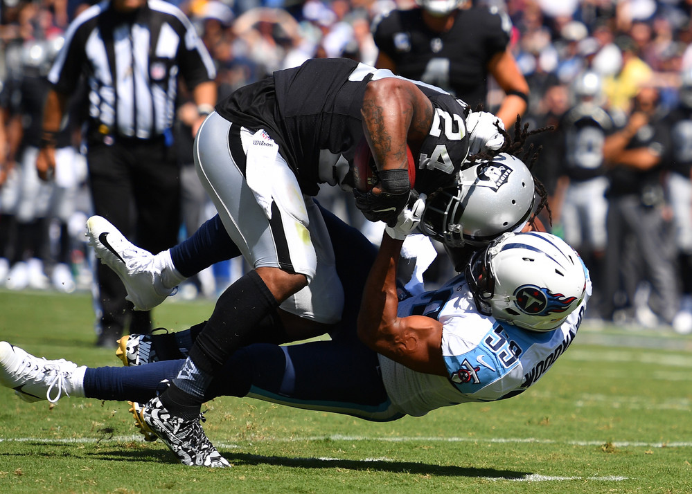 Titans linebacker Wesley Woodyard (59) tackles Raiders running back Marshawn Lynch (24) in the first half of the Raiders at Titans NFL football game on Sept. 10, 2017, at Nissan Stadium in Nashville, Tenn.