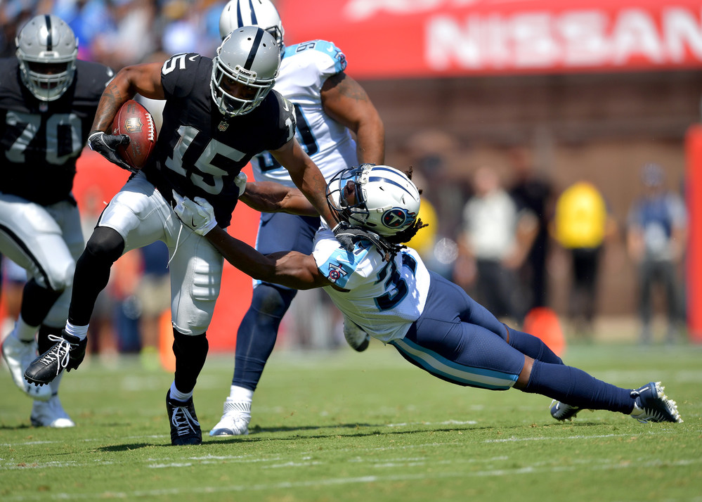 Titans strong safety Johnathan Cyprien (37) cannot hold onto Raiders wide receiver Michael Crabtree (15) in the first half of the Raiders at Titans NFL football game on Sept. 10, 2017, at Nissan Stadium in Nashville, Tenn.