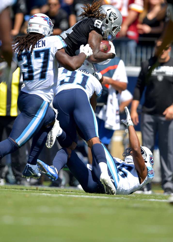 Titans free safety Kevin Byard (31) and strong safety Johnathan Cyprien (37) tackle Raiders wide receiver Cordarrelle Patterson (84) during the first half of the\ Raiders at Titans NFL football game on Sept. 10, 2017, at Nissan Stadium in Nashville, Tenn.